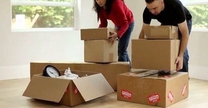 Two people lifting moving boxes.