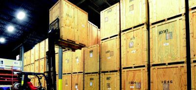 Crane lifting boxes in warehouse.